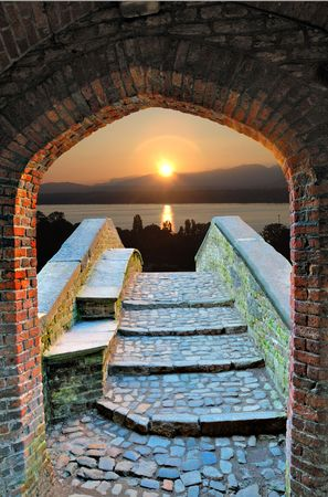 Rising Sun on lake over footbridge seen through medieval doorway. Stock Photo