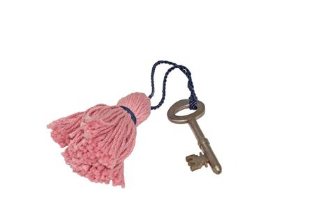 Old brass door key tied to pink tassel with a dark blue cord isolated on white background.
