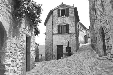 Black and White picture of bakery at the intersection of two cobblestone streets in an old French mountain village.