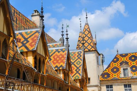 Colorful mosaic tiled roofs of the town hall in Beaune, France. Stock Photo
