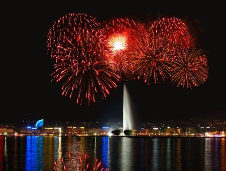 Genève bord du lac avec feu d'artifice lumières de la ville et le Jet d'Eau dans le centre.