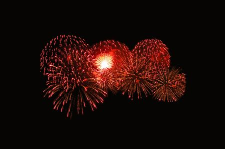 Aerial fireworks display with large red star bursts.
