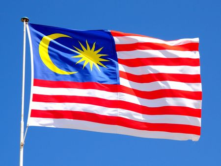 Malaysian Flag fluttering in a brisk breeze against a bright blue sky.