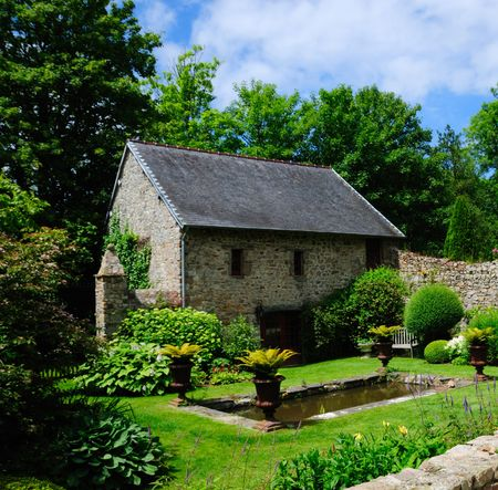 Old Stone cottage and fish pond in an ornamental garden. Stock Photo