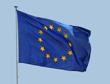 European Union flag fluttering in a brisk breeze against a blue sky.