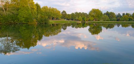 Summer scene of a lake in a green park with late afternoon reflection of clouds and sky.