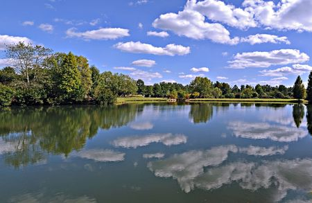 Lake in a park reflecting a blue sky with small clouds stretching to the horizon.