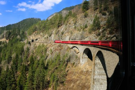 Passenger train crossing a bridge in the Swiss Alps.