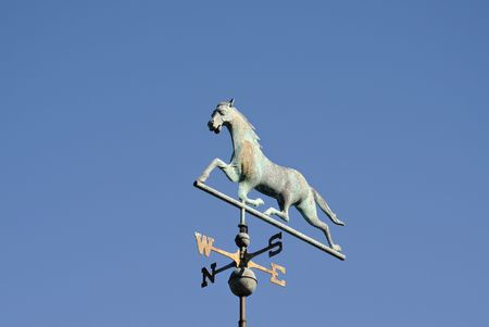 Weathervane with trotting horse against a bright blue sky. Stock Photo