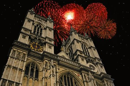 Towers of Westminster Abbey against a  blue sky with clouds with holiday fireworks exploding in the background.