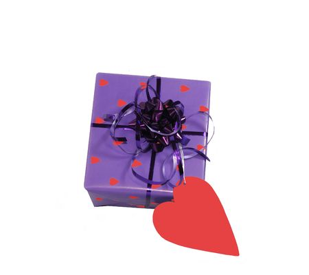 Valentine gift wrapped in purple paper with red hearts, ribbon and bow