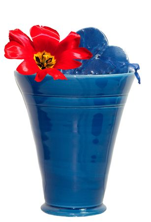 Blue ceramic vase with a bright red tulip and blue ceramic heart.