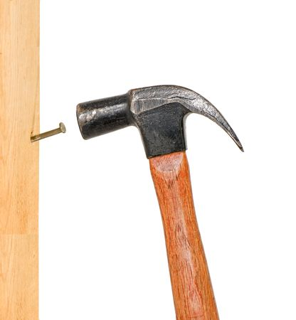 Hammer pounding a nail in a wooden board. Stock Photo
