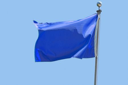 Blue flag flying in a stiff breeze against a clear blue sky. Stock Photo