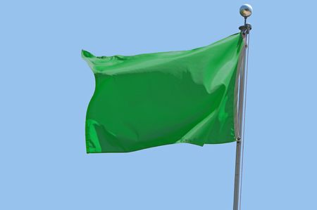 Green flag flying in a stiff breeze against a clear blue sky.
