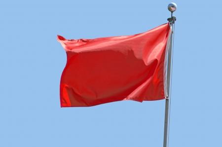 flag: Rode vlag in een stijve wind tegen een heldere blauwe hemel.