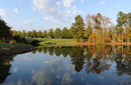 Small lake in Fall with sky and trees reflected on its surface.