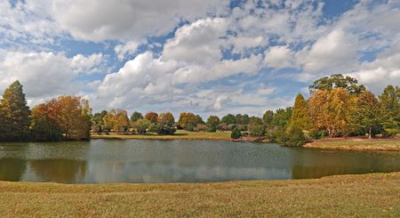 Lake in Fall with dramatic cloud flecked sky and trees and countryside in the background.