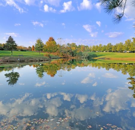 Small pond in Fall with sky and trees reflected on its surface.