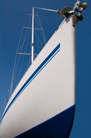 Prow of a sailboat in drydock against a bright blue sky.