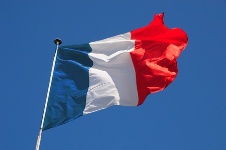French flag fluttering in a brisk breeze against a bright blue sky.