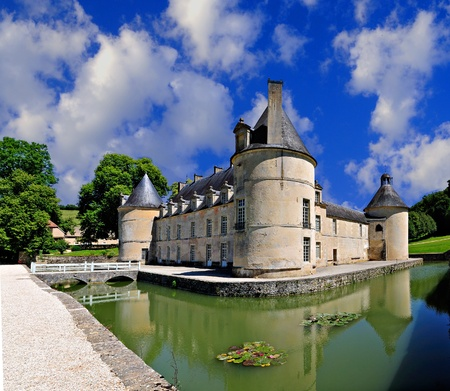 French Chateau of Bussy Rabutin in Burgundy France from the rear showing the moat and dramatic sky.