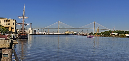 Savannah Georgia riverfront showing the Talmadge bridge, passenger ferry, old schooner and the container port.