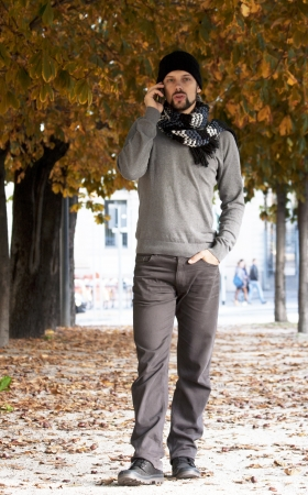 man walking talking on cell phone in autumn photo
