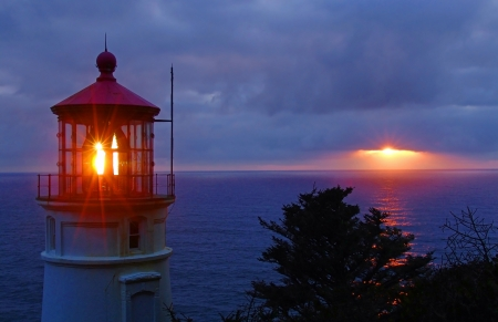 peaking: Sunset peaking from behind the clouds as the light from the Heceta Head Lighthouse passes