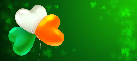 St Patricks Day. Glossy heart-shaped balloons painted in the colors of the Irish flag. Blurred background with leaves of shamrock. Nice background for greeting card, banner, poster or flyer.