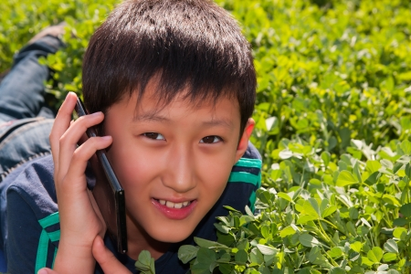 teenager boy lying on the grass and speaking via sellphone Stock Photo - 18567653