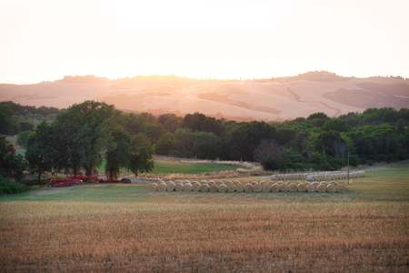 Photo of a farm in tuscany at the sunset time