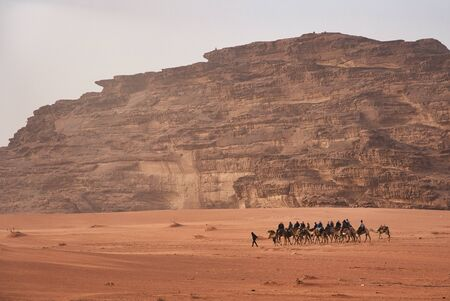 Photo of bedouins crossing the desert in camels at sunset time