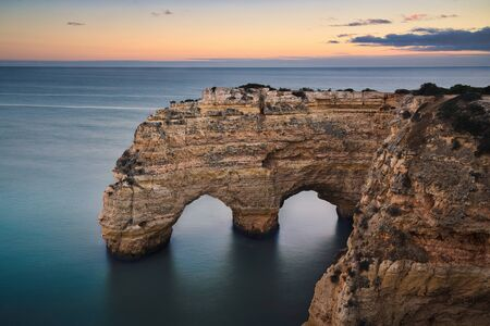Photo of the natural arch in Faro Portugal at the sunset time.