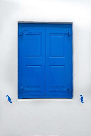 Photo of a blue window in the greek island mikonos