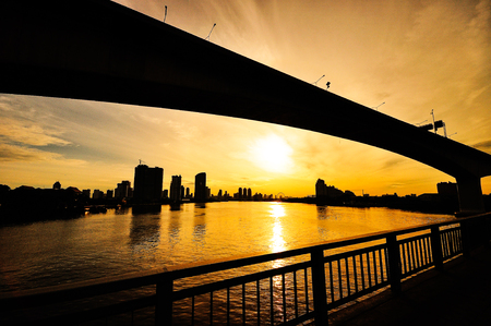 The solid picture of the river bridge in the big city at sunrise.