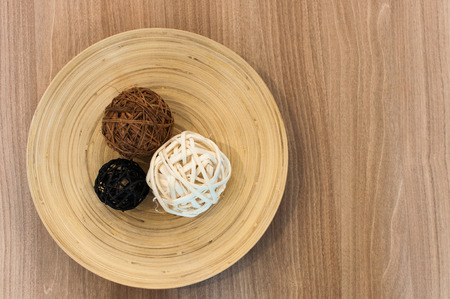 Three spherical shapes placed in a wooden dish for decorating.