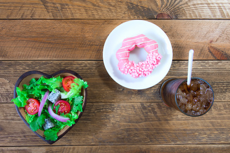 Salad in a bowl made of heart-shaped wood, compared to donut in white ceramic dishes and soft drinks. All laid on a vintage brown wooden floor. 版權商用圖片