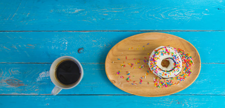 Donut with white cream topped with chocolate and sprinkle with sugar in a variety of colors in a wooden tray, and a cup of black coffee, Placed on a blue vintage wooden table.