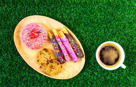 Chocolate chip cookies and donuts have a lot of topping. Placed on a wooden tray. Coupled with black coffee in a white ceramic cup. All were placed on artificial grass.