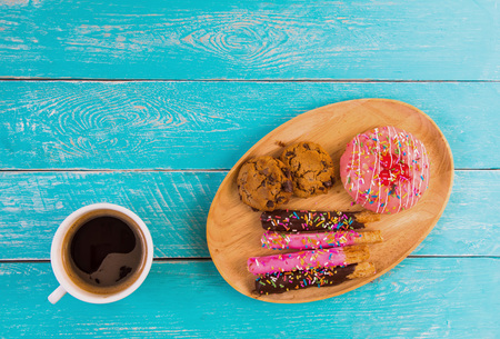 Chocolate chip cookies and donuts have a lot of topping. Placed on a wooden tray. Coupled with black coffee in a white ceramic cup. All were placed on vintage blue wooden background.