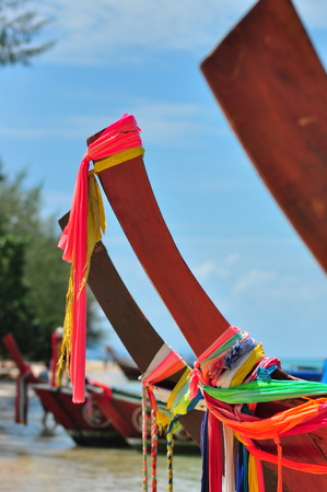 The head of a marine tour boat in Thailand is made of hardwood, curved, decorated with colorful fabrics according to faith. 免版税图像