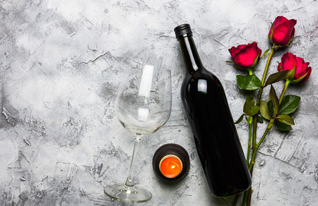 A bottle of red wine with a glass, placed on the side of the candle and a group of red roses on the surface of white and gray With copy space for the Valentines Day festival. Reklamní fotografie - 120781153