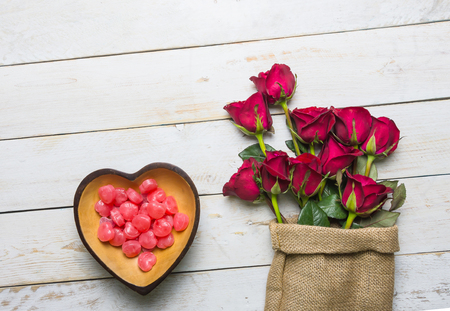 Red roses placed on a bowl of red heart-shaped candy on a white vintage wooden background with a copy space for the Valentine's Day festival.