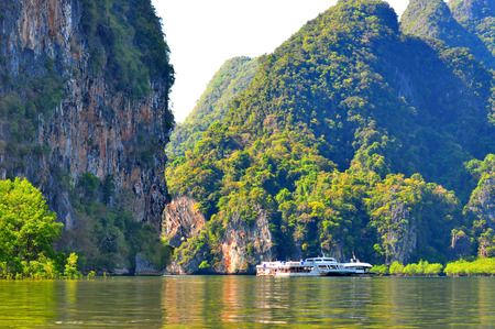 The medium-sized tourist boat brings tourists to the sea and the large rocks that are rich with trees.