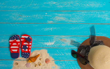 Beach Accessories for Summer Concept. Such as sandals, shells, hats. And sunglasses lay on the abrasive blue wood texture,with copy space. Reklamní fotografie - 120781191