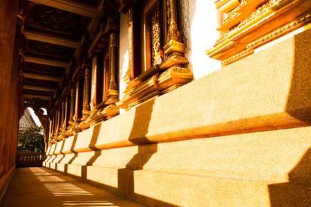 The silhouette of Thai architectural pillars over the sandy corridor.