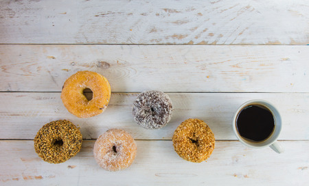 Donut coated with  sugars,coconut and nuts,appetite. Layered on a white vintage wooden floor,with a cup of black coffee.