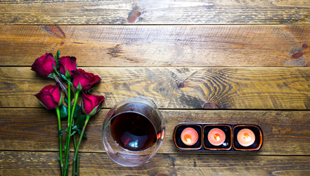 Roses and red wines with candles Placed on a vintage brown wooden background. Reklamní fotografie