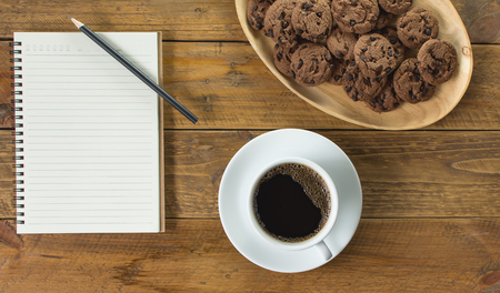 Black coffee in white ceramic cup with saucer. With notebook and pencil for notes and wooden tray of chocolate chip cookies. Placed on vintage wooden background.